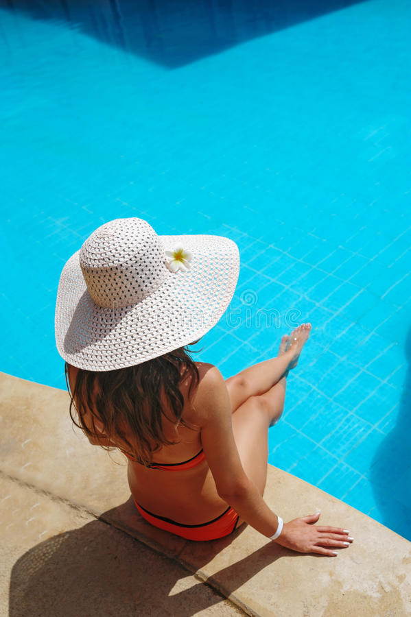 Beautiful young woman at the resort sits on the edge of the pool.  stock images