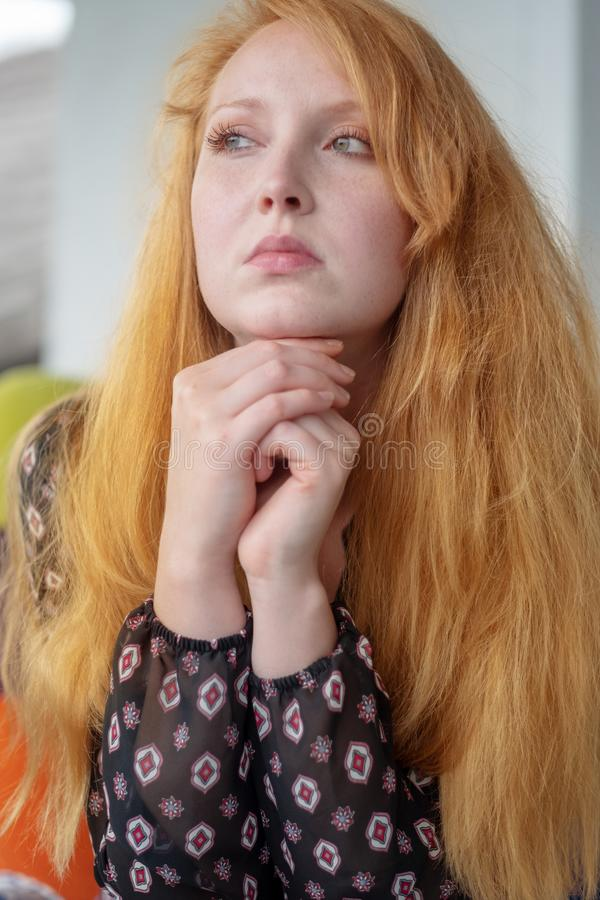 Beautiful young woman resting her head on her hands thoughtfully looks aside royalty free stock image