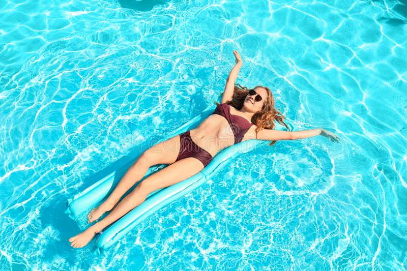 Beautiful young woman resting on inflatable mattress in pool royalty free stock photo