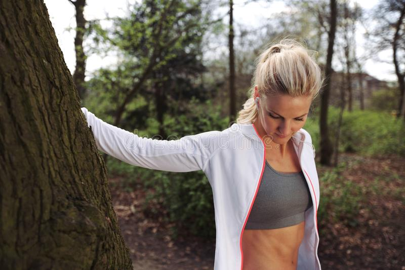 Beautiful young woman resting after jogging in a park. Beautiful young woman resting by a tree after jogging in a park. Fit female athlete taking a break after stock photography