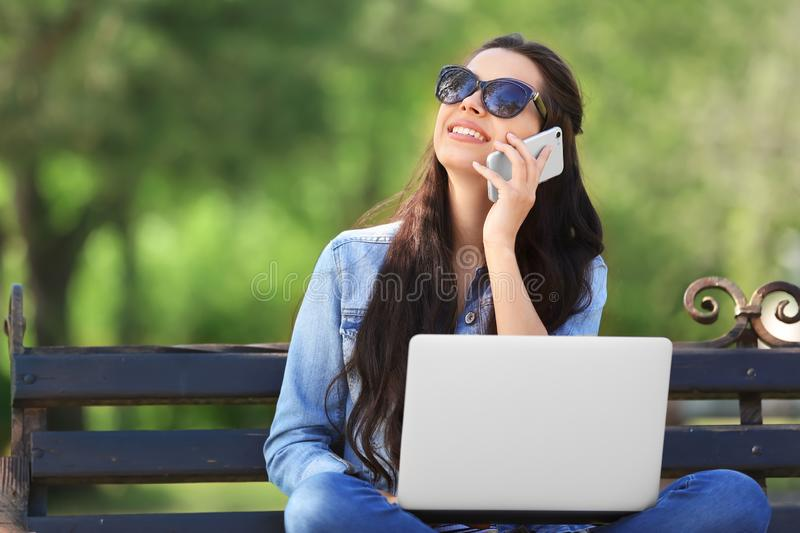 Beautiful young woman resting in park with laptop and mobile phone stock images