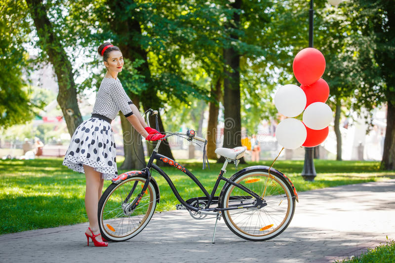 Beautiful young woman retro pin-up style with bicycle royalty free stock photography