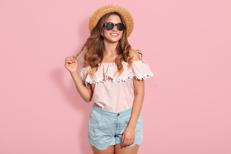 Beautiful young woman in rose summer blouse, blue short, sunglasses and sun hat, pulling her hair aside, being in good mood, ready. For going out with friends stock photos