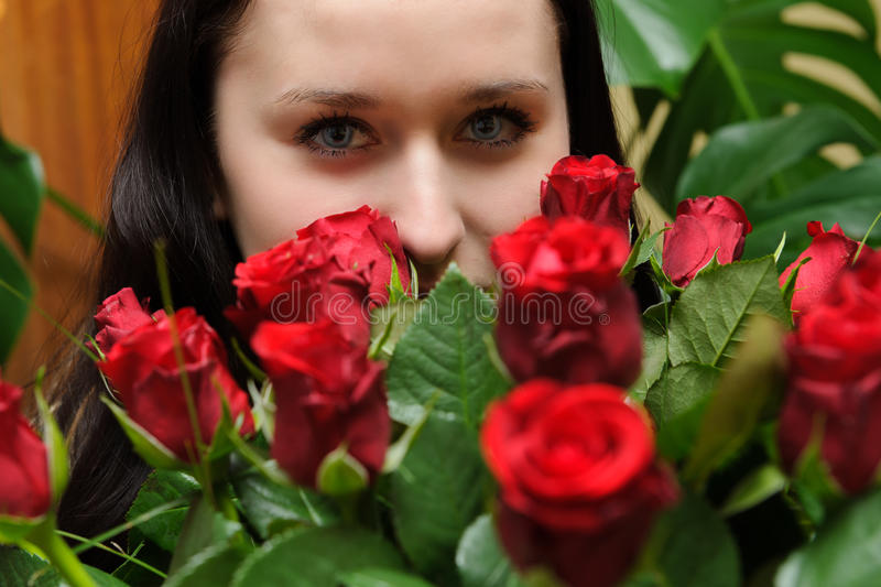 Beautiful young woman with roses and white horse stock image