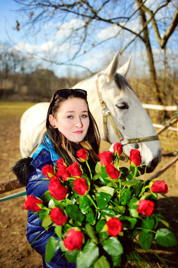 Beautiful young woman with roses and white horse. Beautiful young woman standing with bunch of roses before white horse stock photography
