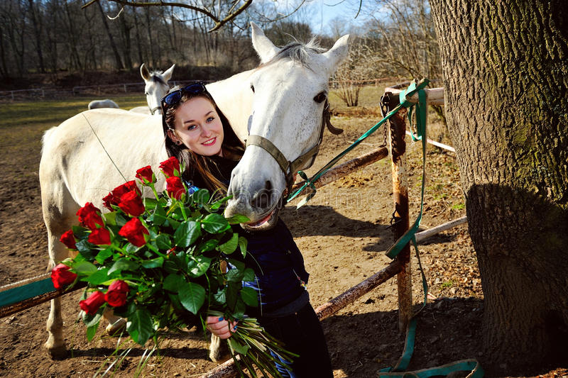 Beautiful young woman with roses and white horse stock images