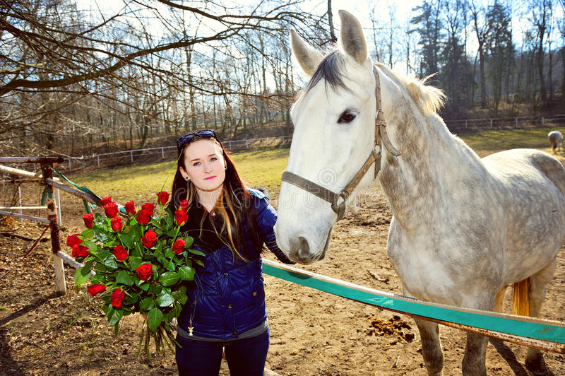 Beautiful young woman with roses and white horse royalty free stock photos