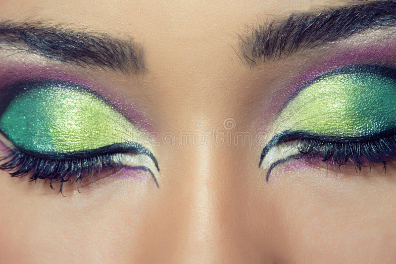 Beautiful young woman's face with colorful makeup royalty free stock images