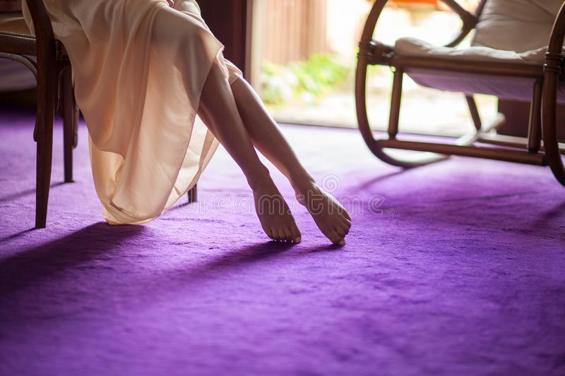 Beautiful young woman`s feet close up at home, soft violet carpet floor. Can be used as background stock images