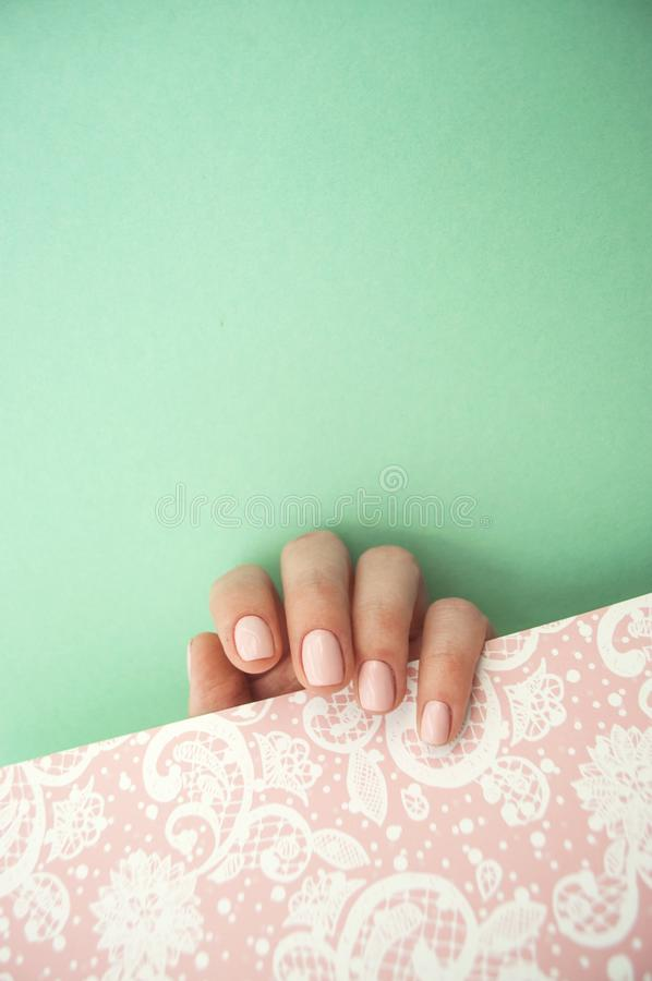 Beautiful young woman`s hand on pink background stock photos