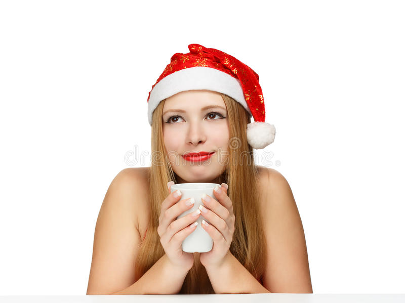 Beautiful young woman in santa claus hat sitting at the table wi. Th white cup isolated on white background stock photography