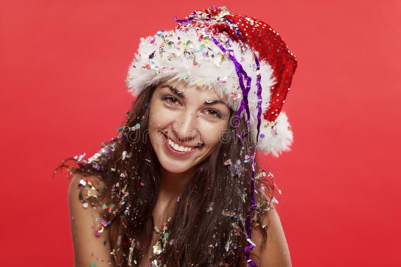 Beautiful young woman in santa claus hat smiling. Christmas tale. Postcard. Red background stock images