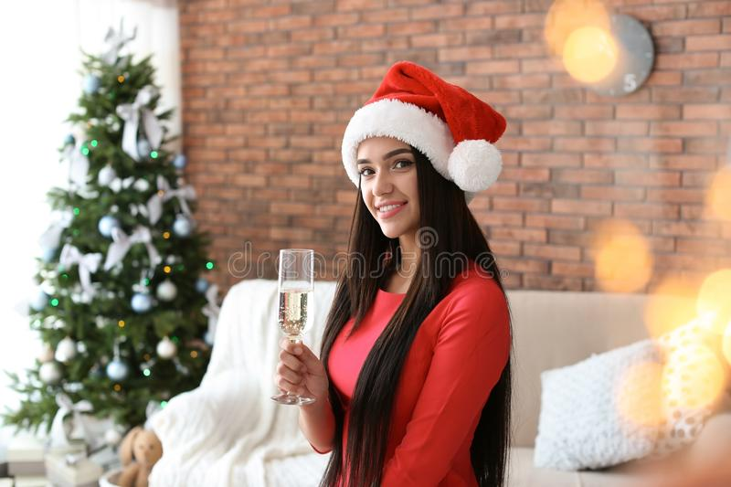 Beautiful young woman in Santa hat with glass royalty free stock images