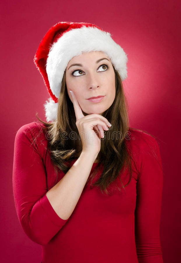 Beautiful young woman with santa hat thinking