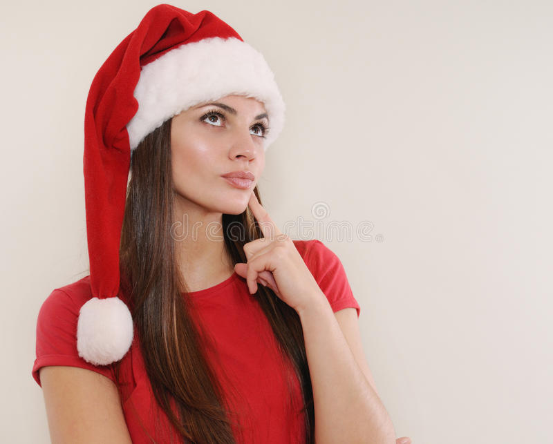 Beautiful young woman in Santa hat thinking about Christmas gift stock photography