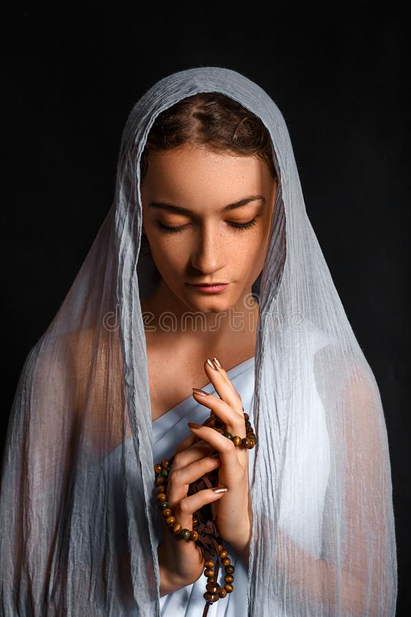 Beautiful young woman with a scarf on her head, and a rosary in her hands, humble look, believing woman stock photo