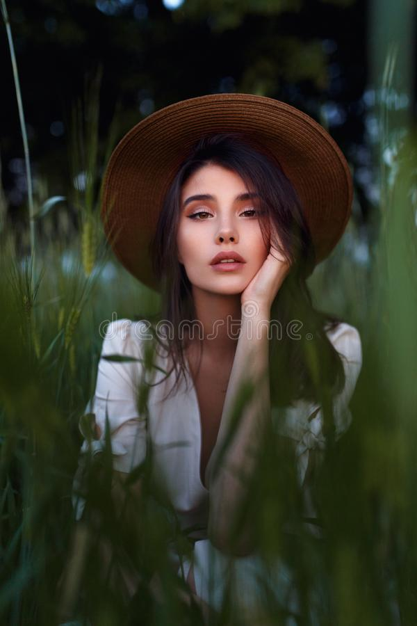 Carefree adorable brunette young woman in romantic outfit, with hand on her face in green field. Care concept. royalty free stock image