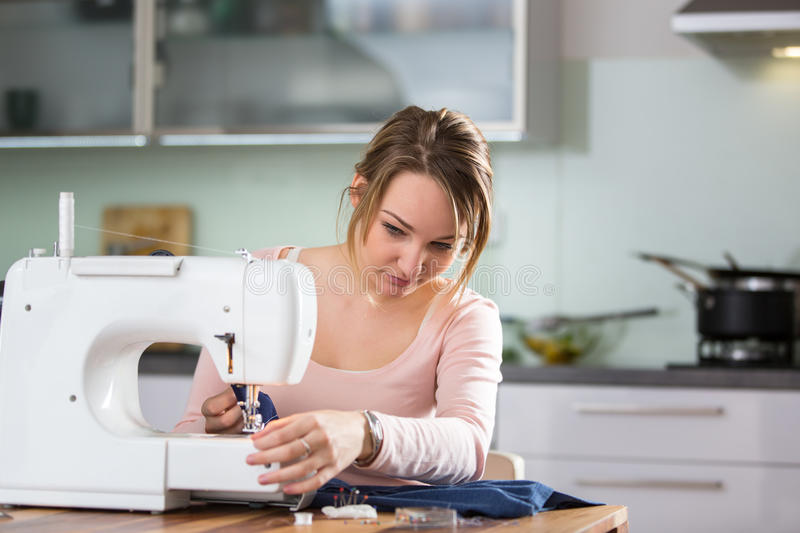 Beautiful young woman sewing clothes with sewing machine royalty free stock photography