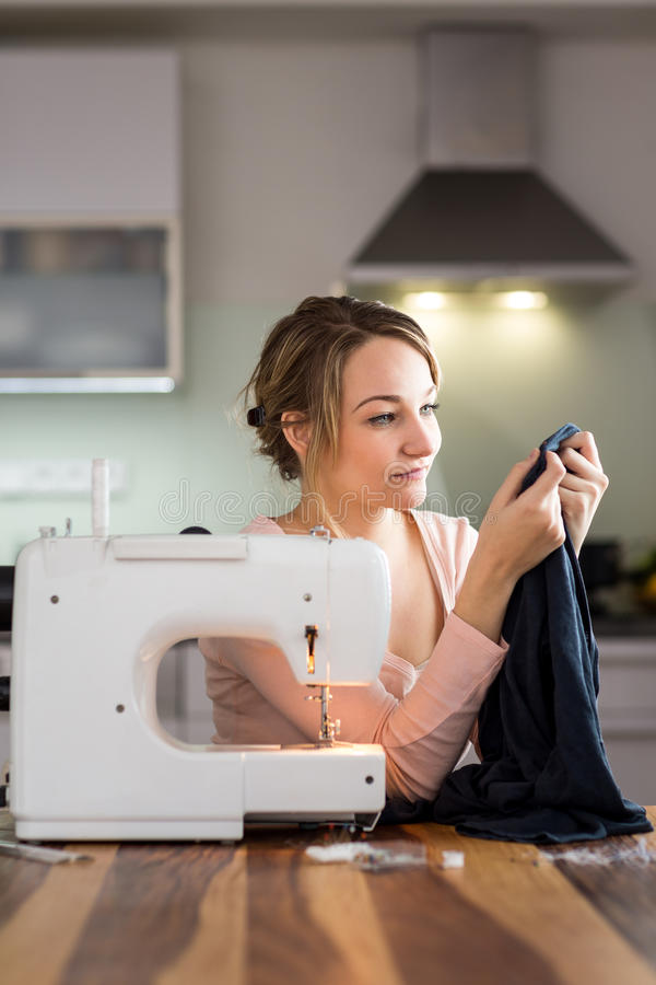 Beautiful young woman sewing clothes with sewing machine royalty free stock images