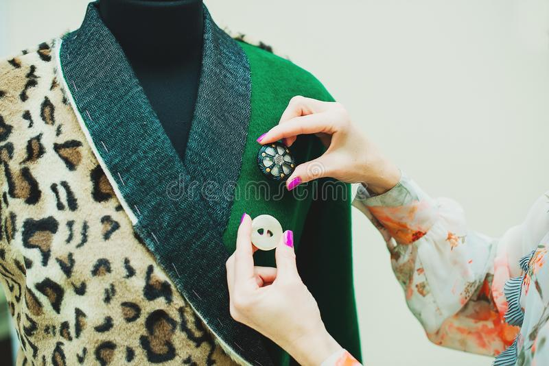 Beautiful young woman sews designer coat. Leopard print coat and green. The seamstress chooses the buttons to the coat stock photography