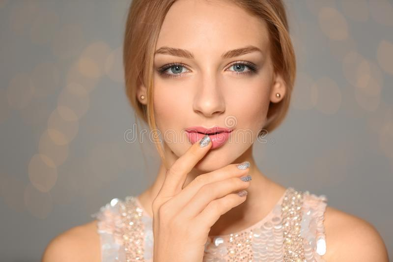 Beautiful young woman with shiny manicure on blurred background. Nail polish trends stock photo