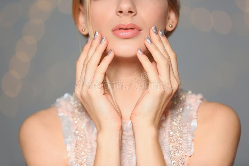 Beautiful young woman with shiny manicure on blurred background. Nail polish trends stock images