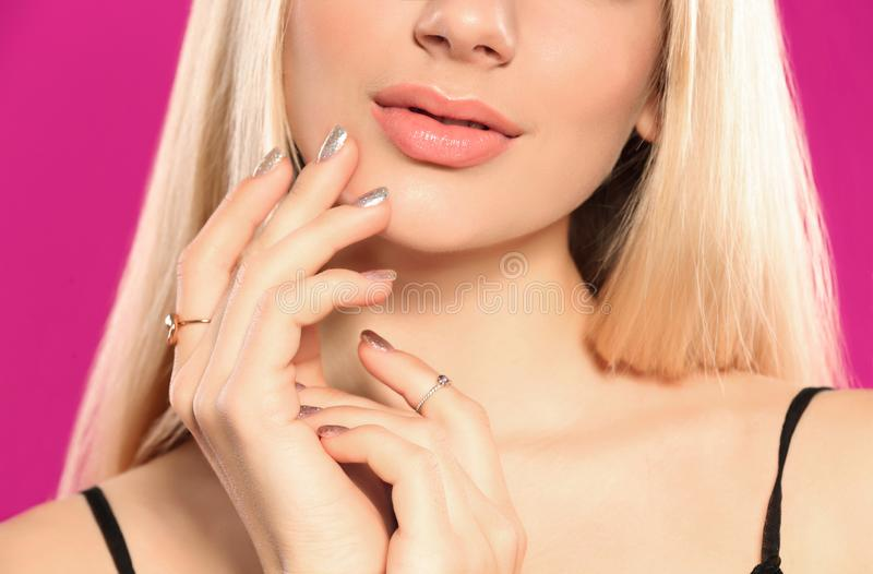 Beautiful young woman with shiny manicure, closeup. Nail polish trends stock photography