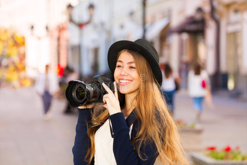 Beautiful young woman shooting with camera stock image
