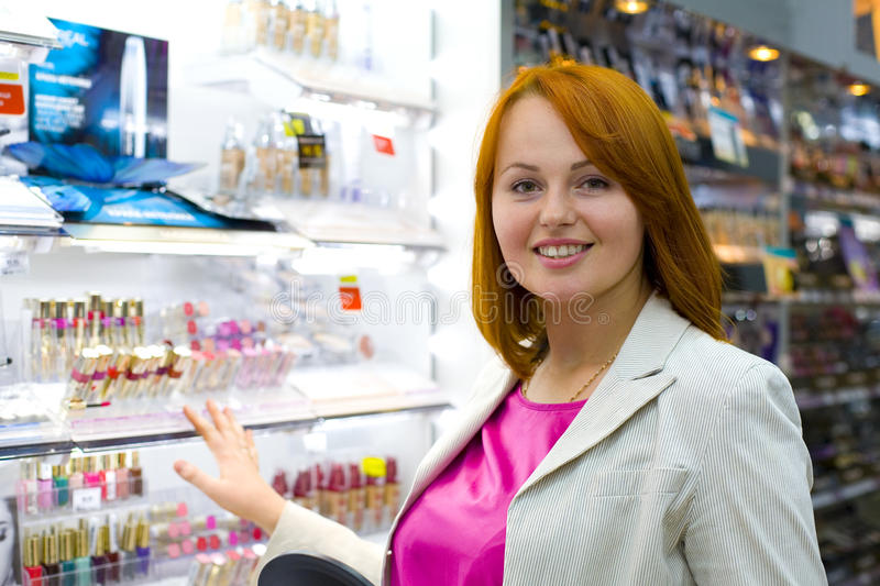 Beautiful young woman in the shop. Beautiful young woman in shop chooses cosmetics stock photos