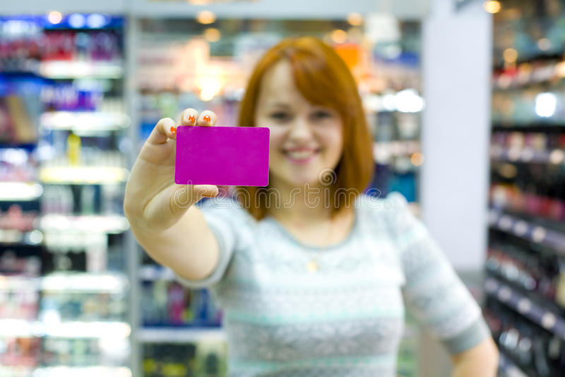 Beautiful young woman in the shop. Young girl in shop of cosmetics holds a credit card in hand stock image