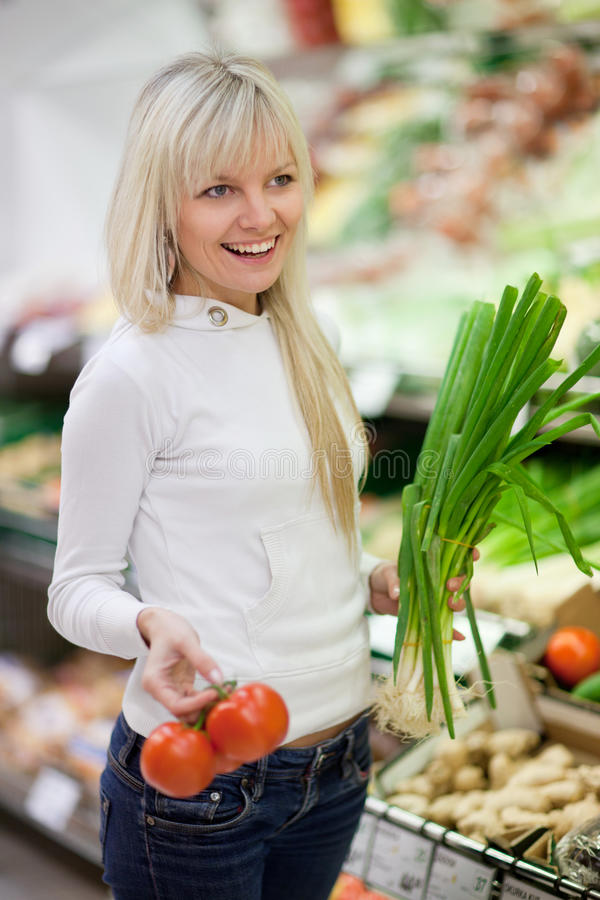 Beautiful young woman shopping. For fruits and vegetables in produce department of a grocery store/supermarket royalty free stock photography