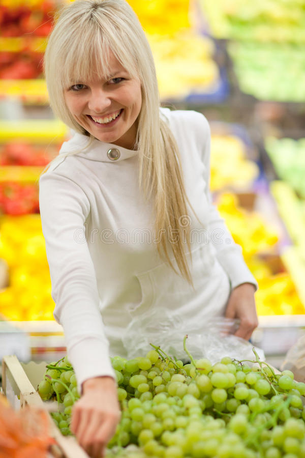 Beautiful young woman shopping. For fruits and vegetables in produce department of a grocery store/supermarket stock image