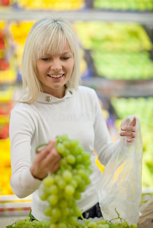 Beautiful young woman shopping. For fruits and vegetables in produce department of a grocery store/supermarket stock photography