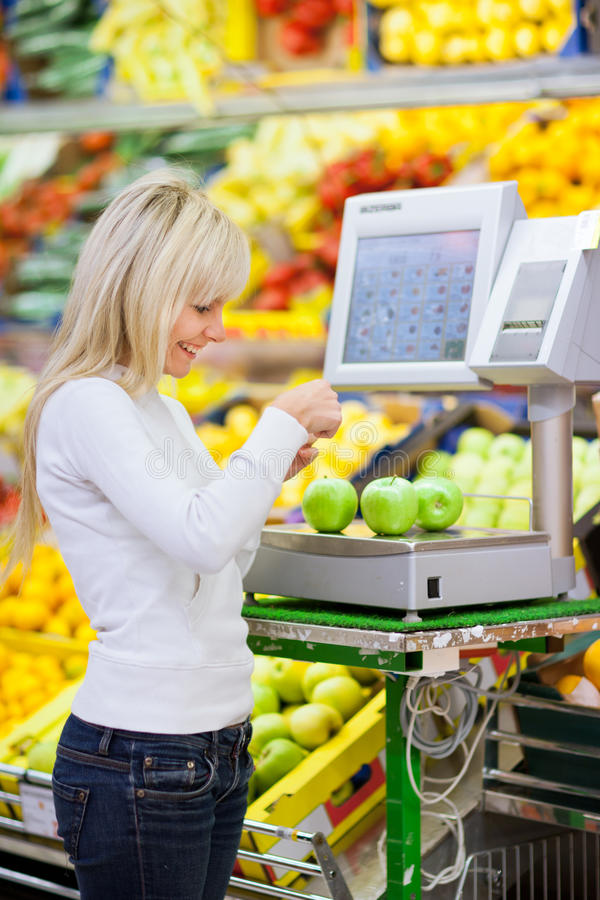 Beautiful young woman shopping. For fruits and vegetables in produce departmant of a grocery store/supermarket (shallow DOF royalty free stock photo