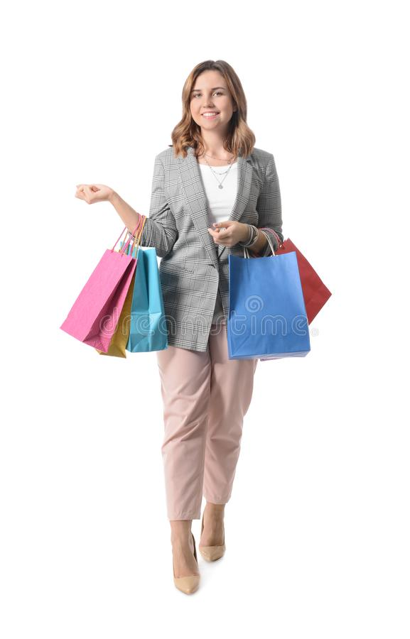 Beautiful young woman with shopping bags on white background stock photo