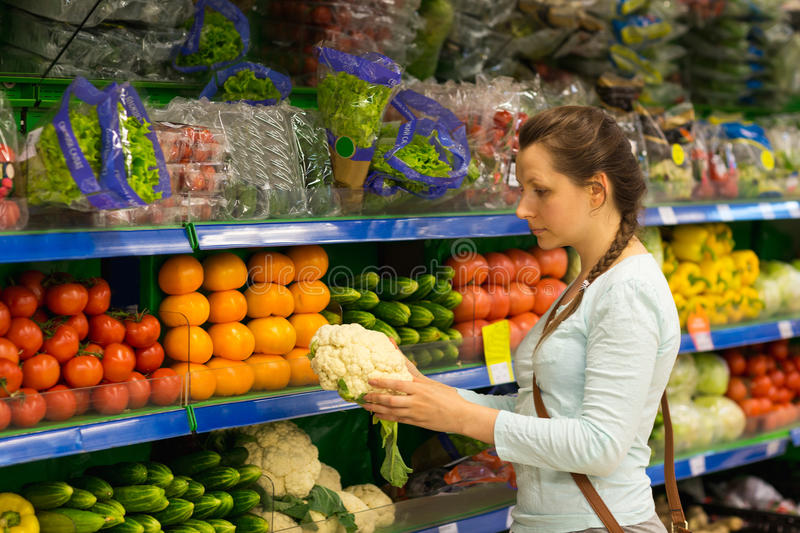 Beautiful young woman shopping for cereal, bulk in a grocery store stock photo