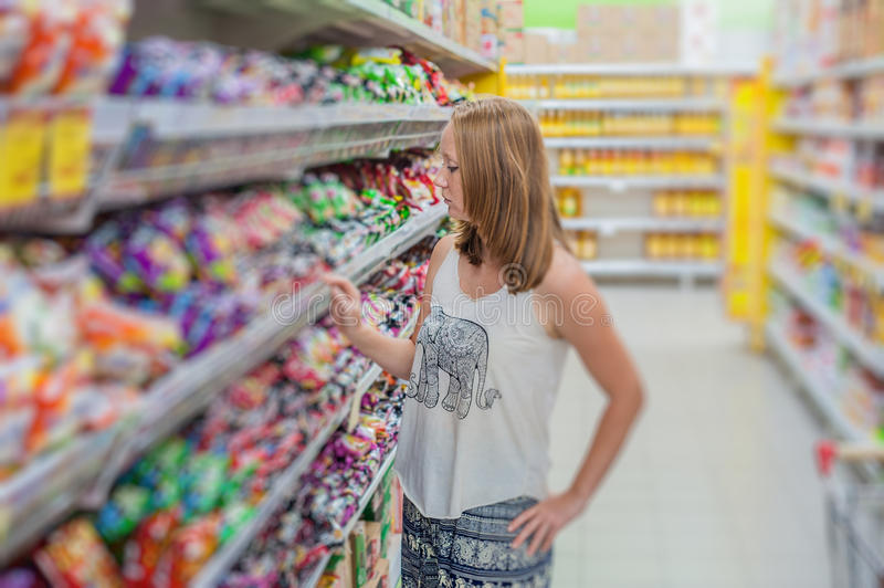 Beautiful young woman shopping for grocery products at a grocery store supermarket royalty free stock photo