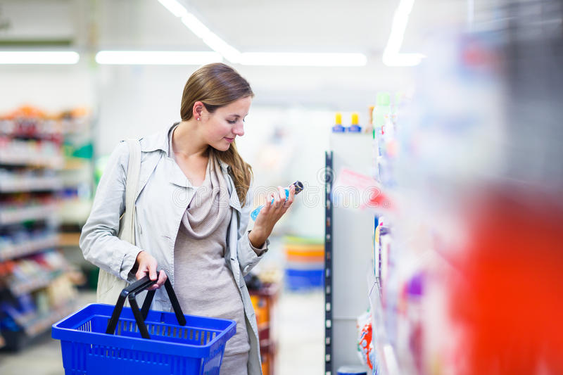 Beautiful young woman shopping in a grocery store/supermarket royalty free stock images
