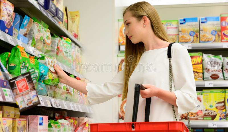 Beautiful young woman shopping in grocery store, taking food of shelf royalty free stock images