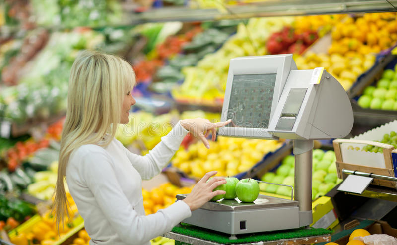 Beautiful young woman shopping for vegetables. Beautiful young woman shopping for fruits and vegetables in produce department of a grocery store/supermarket royalty free stock photos