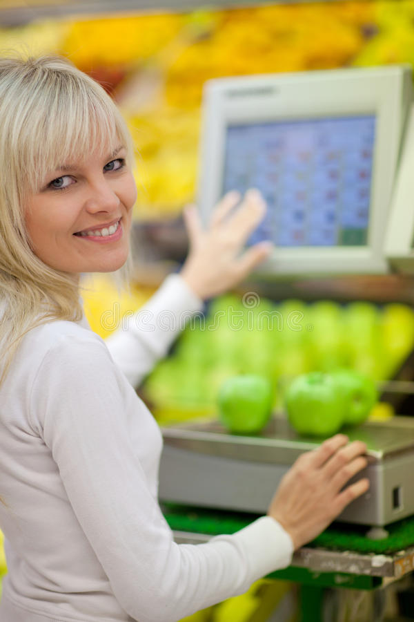 Beautiful young woman shopping for vegetables. Beautiful young woman shopping for fruits and vegetables in produce department of a grocery store/supermarket royalty free stock photo