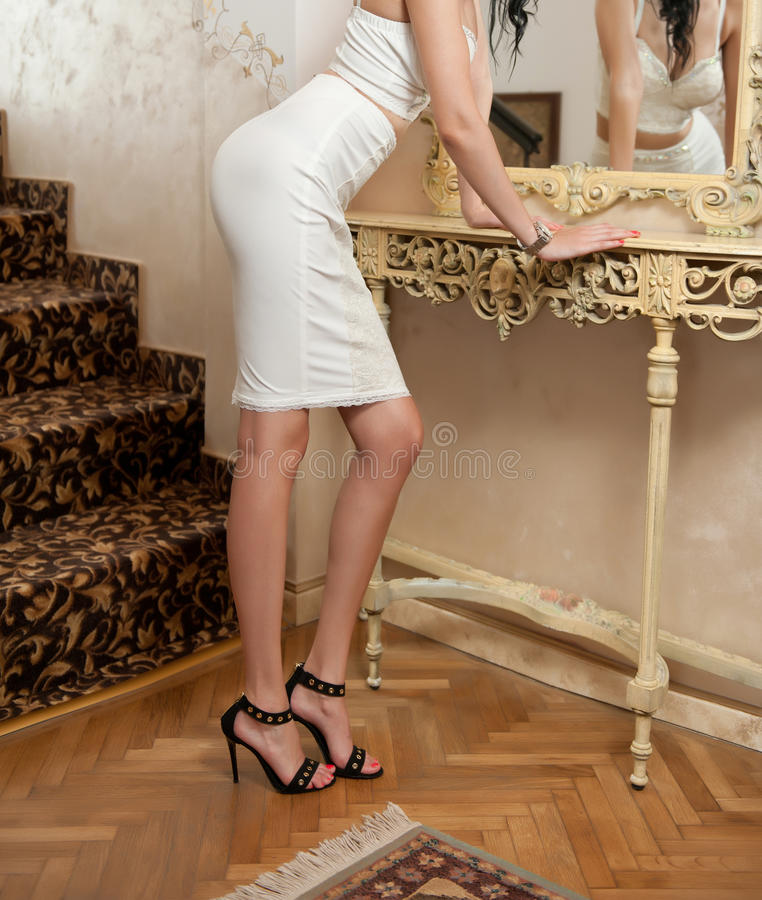 Beautiful young woman in short white tight fit skirt and corset looking into mirror. Perfect body female in front of a mirror royalty free stock photos
