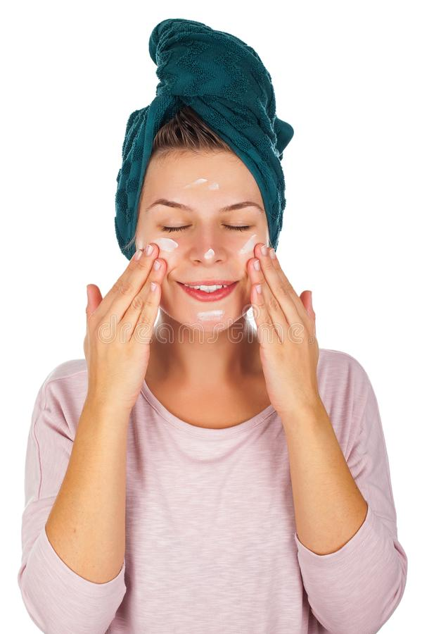 Woman with bathtowel appying face cream royalty free stock photography
