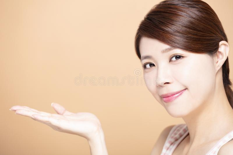 Beautiful young woman showing beauty product empty space on hand royalty free stock image