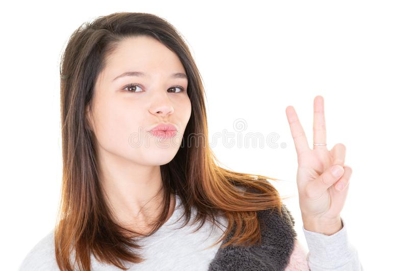 Beautiful young woman showing peace victory sign in white background stock image