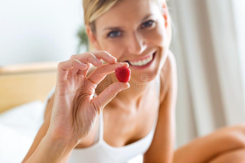 Beautiful young woman showing a raspberry and looking at camera in the bedroom. royalty free stock photo