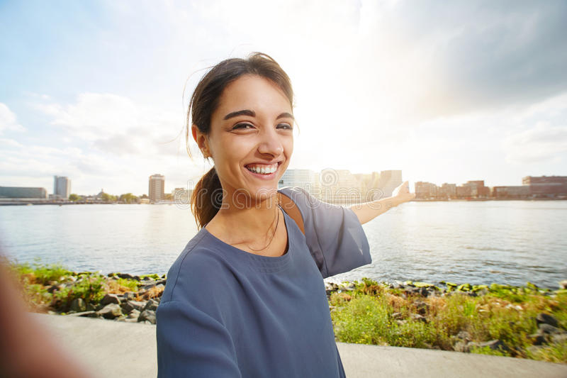 Beautiful young woman showing urban skyline. Portrait of beautiful young woman standing outdoors and pointing at urban skyline royalty free stock image