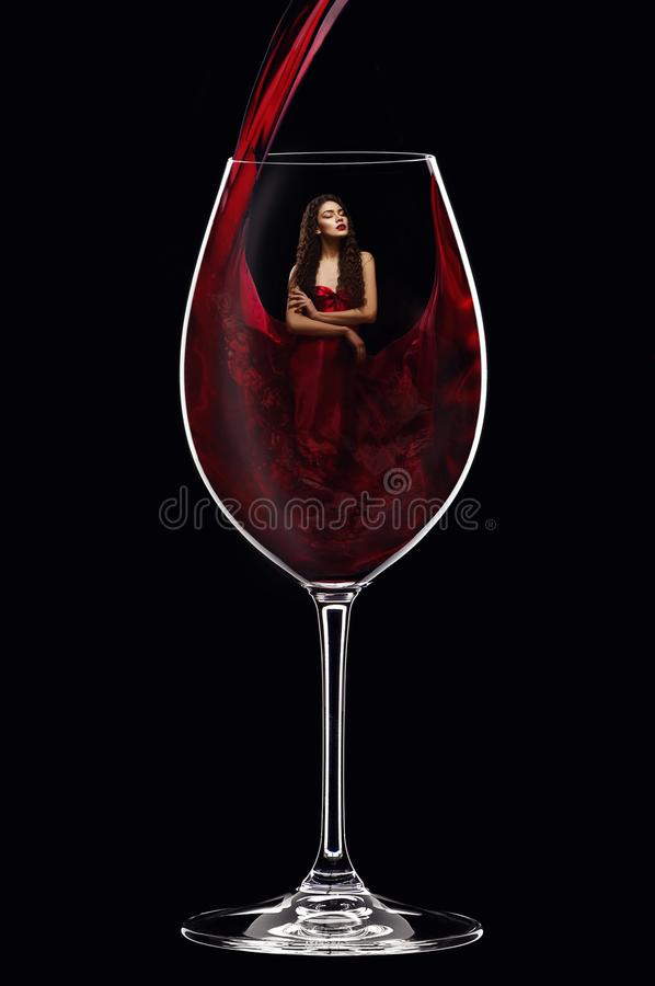 Girl in red dress inside wine glass royalty free stock photos