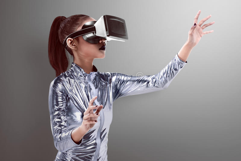 Beautiful young woman in silver latex costume and VR headset royalty free stock images