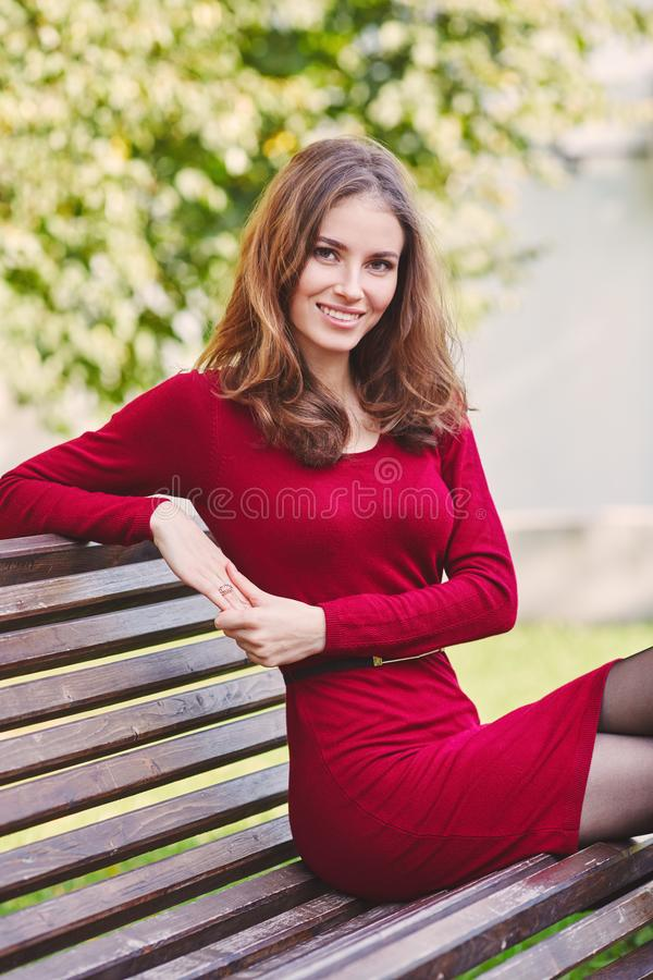 Beautiful young woman sits on a bench. Outdoor portrait royalty free stock photo